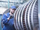 Engineer measuring high pressure steam turbine blade in workshop - CUF34974