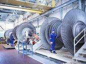 Engineers with low pressure steam turbines in repair bays in workshop - CUF34977