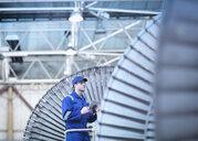 Engineer inspecting steam turbine in repair bay - CUF34980