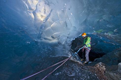 Mature woman descending into Ice cave on the Svinafellsjokull glacier, Vatnajokull National Park, Iceland - CUF35226