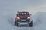 Mature woman driving red pick up truck on snow covered road, Vikurskard, North Iceland - CUF35229