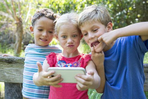 Three children in garden taking selfie on smartphone - CUF35256
