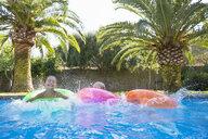 Three children splashing on inflatable rings in garden swimming pool - CUF35268
