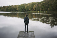 Rear view of young man standing on river pier - CUF35292