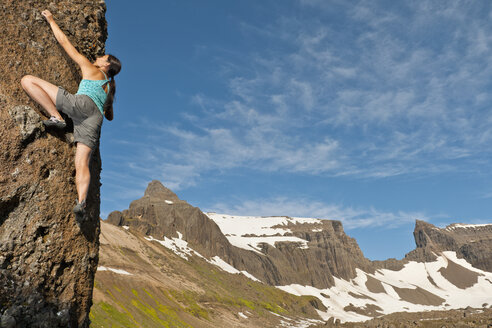 Female climber scaling steep rock with Dyrfjoll at the horizon, East Iceland, Iceland - CUF35298
