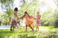 Five girls playing ring a ring a roses in garden - CUF35322