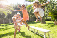 Five energetic girls jumping from garden bench - CUF35325