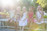 Portrait of five girls sitting on garden bench - CUF35328