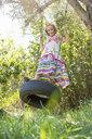 Portrait of girl standing swinging on tree swing in garden - CUF35340