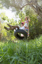 Two girls sitting and standing on tree swing in garden - CUF35343