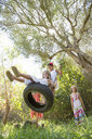 Low angle view of four girls playing on tree tire swing in garden - CUF35346