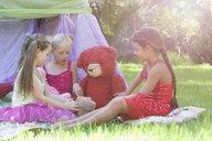 Three girls playing with teddy bears in garden - CUF35349