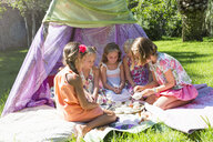 Five girls playing with toy tea set in front of teepee - CUF35352