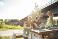 Three young friends drinking beer on riverside picnic bench - CUF35358