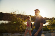 Young couple strolling along riverside at sunset - CUF35364