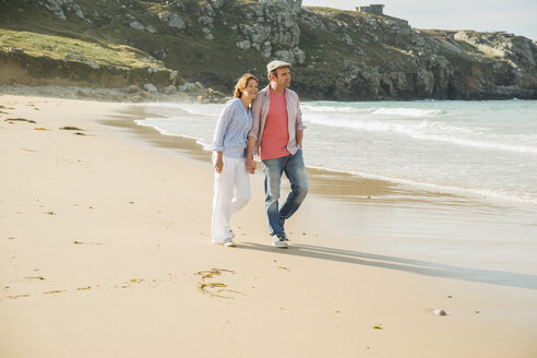 Mature couple holding hands strolling on beach, Camaret-sur-mer, Brittany, France - CUF35370
