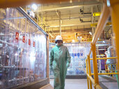 Engineer walking in acid and caustic plant in power station - CUF35409