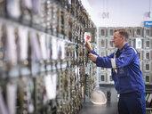 Engineer selecting equipment keys in power station - CUF35511