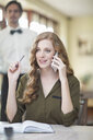 Young businesswoman chatting on smartphone in restaurant - CUF35700