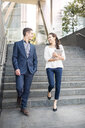 Rear view of young businessman and woman walking down stairway, London, UK - CUF35709