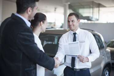 Mid adult couple making deal with salesman in car dealership - CUF35733