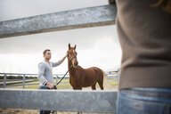 Young woman watching stablehand with horse in paddock ring - CUF35757