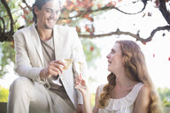 Couple toasting each other with champagne in garden restaurant - CUF35763