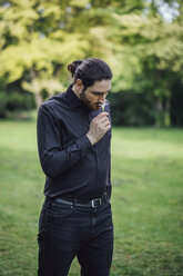 Young man, dressed in black, standing in park, smelling flower - JSCF00102