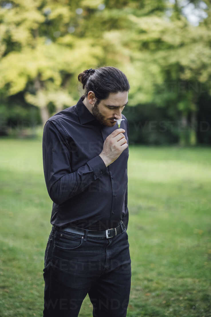 Young man, dressed in black, standing in park, smelling flower - JSCF00102 - Jonathan Schöps/Westend61