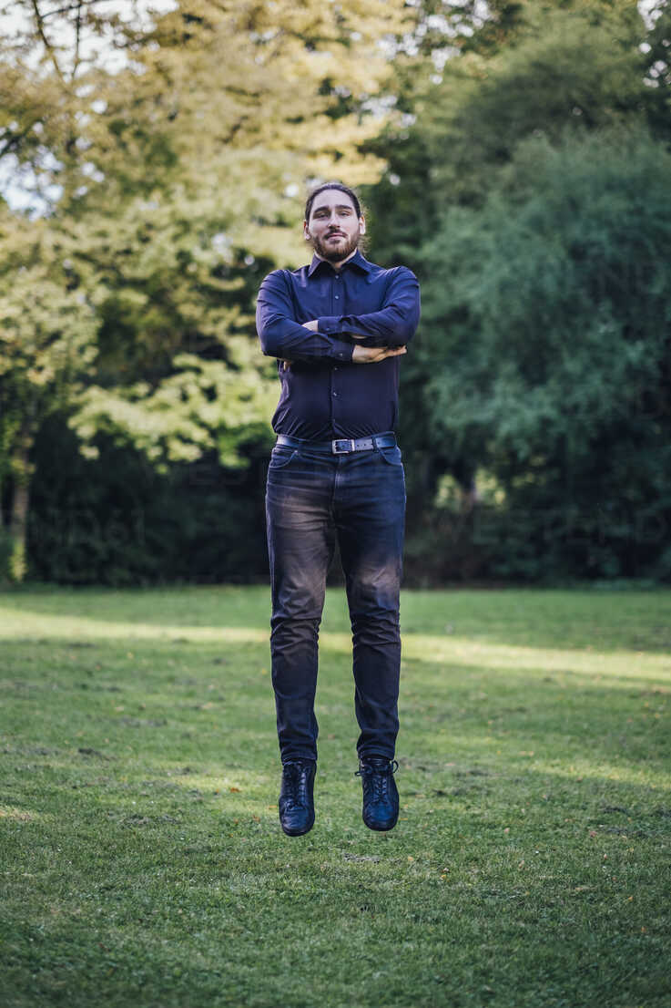 Young businessman levitating in park - JSCF00105 - Jonathan Schöps/Westend61