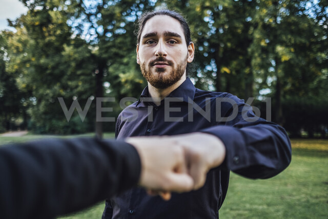 Young businessman greeting business partner in a park, negotiating business transactions - JSCF00108