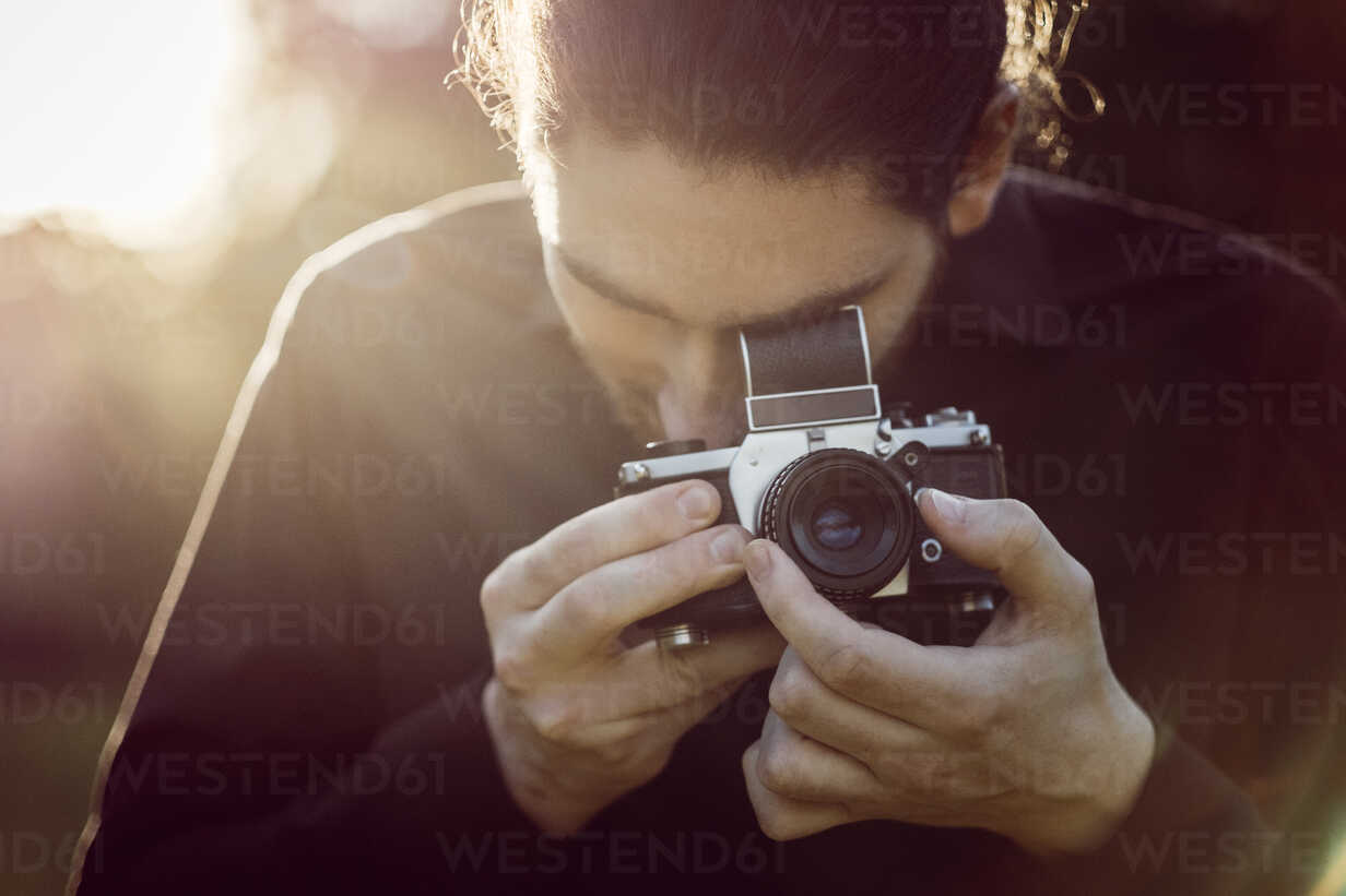 Young man photographing with analogue camera - JSCF00111 - Jonathan Schöps/Westend61