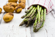 Green asparagus and potatoes on white wood - LVF07153
