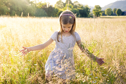 Young girl walking through field at summer evening - LVF07159