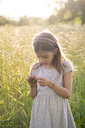 Young girl standing in field at summer evening - LVF07162