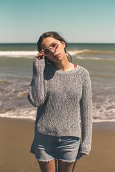 Spain, portrait of young woman wearing sunglasses standing on the beach - ACPF00050