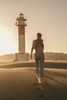 Spain, back view of young woman walking to lighthouse at sunset - ACPF00056