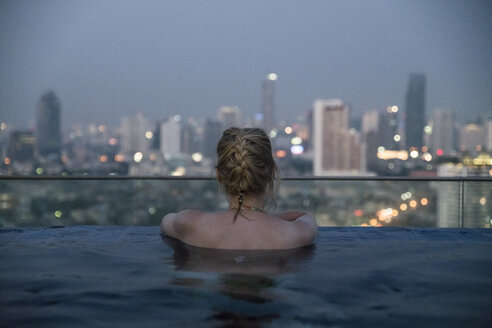 Thailand, Bangkok, back view of woman bathing in Infinity Pool looking at skyline - CHPF00489