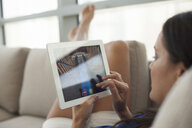 Close up of young woman on sofa using digital tablet - CUF35978