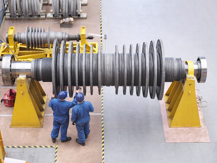Engineers inspecting turbine  during power station outage, high angle view - CUF36095