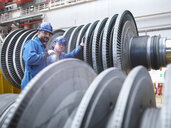 Engineers inspecting turbine during power station outage, portrait - CUF36101