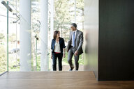 Businessman and woman walking up stairs - CUF36116