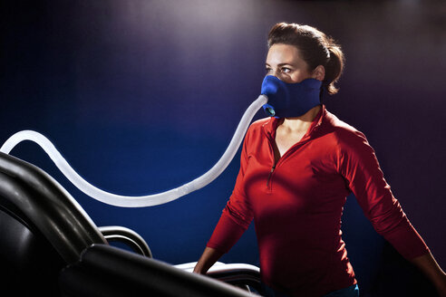 Mid adult woman with face mask on gym treadmill in altitude centre - CUF36218