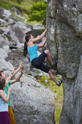 Mature female climber bouldering on RAC boulders,  watched by friends, Snowdonia, North Wales, UK - CUF36305