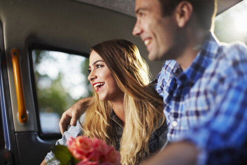 Young woman with boyfriend and bunch of roses in city taxi - CUF36314