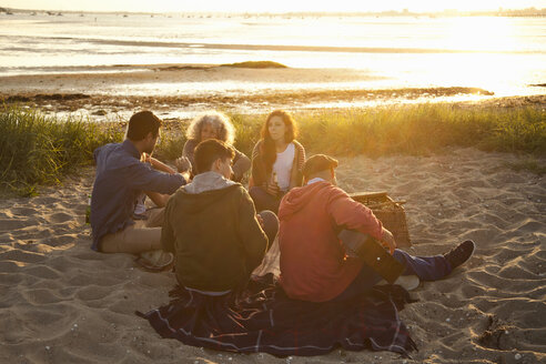 Adult friends picnicing at sunset on Bournemouth beach, Dorset, UK - CUF36350