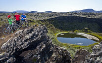 Cyclists looking out into a craterlake, Nesjavellir, Thingvellir national park, Iceland - CUF36431