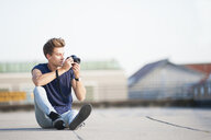 Young man on rooftop, holding camera - CUF36476