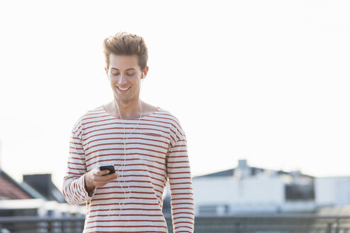 Young man on rooftop, wearing earphones and holding smartphone - CUF36479
