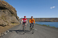 Cyclists cycling on road next to Kleifarvatn, Reykjanes, South West Iceland - CUF36509